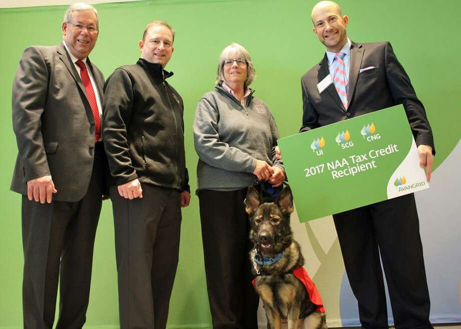 Richard LoPresti, left, and Al Carbone, right, of AVANGRID, congratulate Mark McGrath, Susan Greer and canine Olive of the Fidelco Guide Dog Foundation after presenting a check for $4,641.99 to help the nonprofit with energy-efficient lighting upgrades. Photo: Contributed Photo / Contributed Photo / New Haven Register contributed