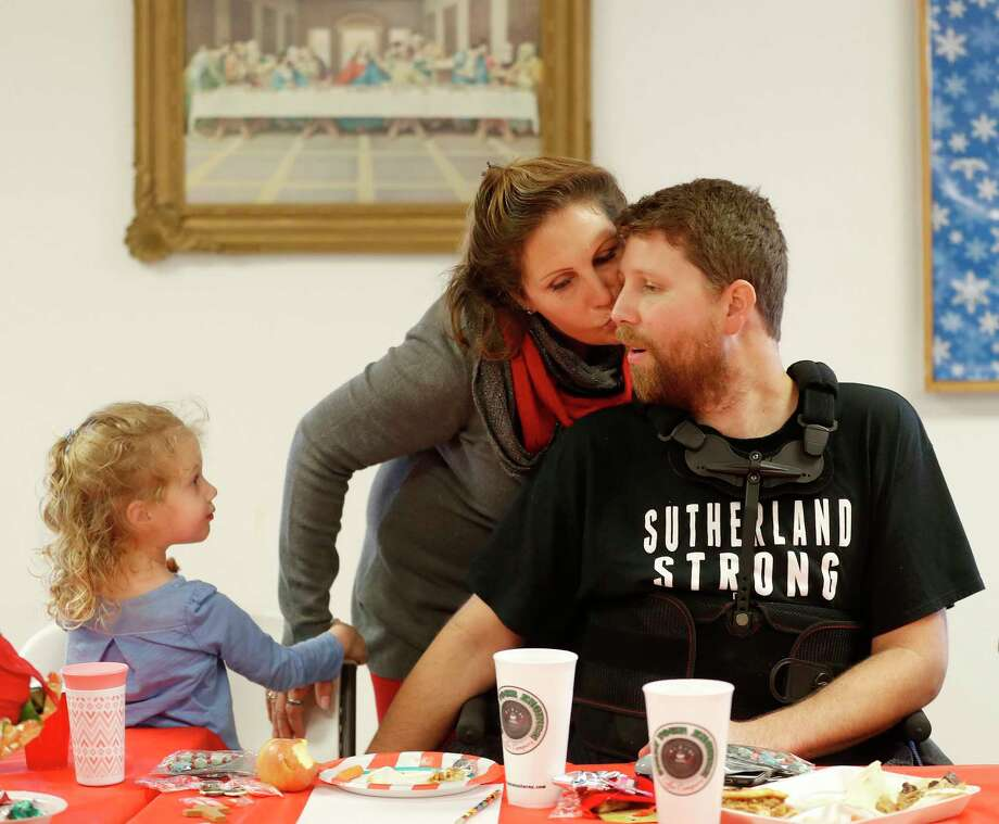Julie Workman kisses her son, Kris, with his daughter Eevee, at a potluck at the Sutherland Springs First Baptist Church. Photo: Karen Warren, Staff / © 2017 Houston Chronicle
