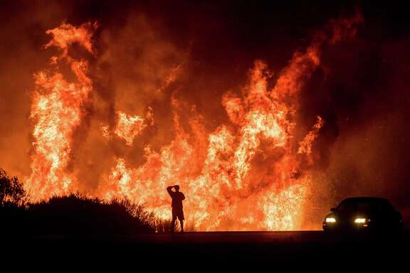 A motorist watches flames leap above Highway 101 north of Ventura, Calif. The Thomas fire has scorched 273,400 acres, or about 427 square miles of coastal foothills and national forest in Ventura and Santa Barbara counties.