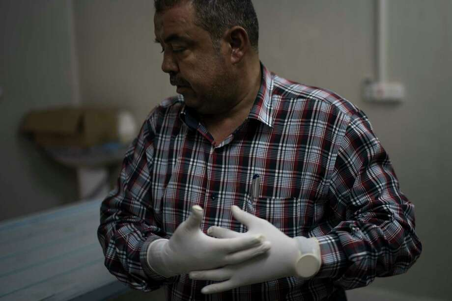 In this Nov. 8, 2017 photo, chief medical assistant Raid Jassim adjusts his gloves before inspecting a body in a morgue in Mosul, Iraq. The morgue staff saw the worst of what the Islamic State group was capable of inflicting on a human being. Though terrorized, they managed moments of humanity and sometimes defiance (AP Photo/Felipe Dana) Photo: Felipe Dana / Copyright 2017 The Associated Press. All rights reserved.