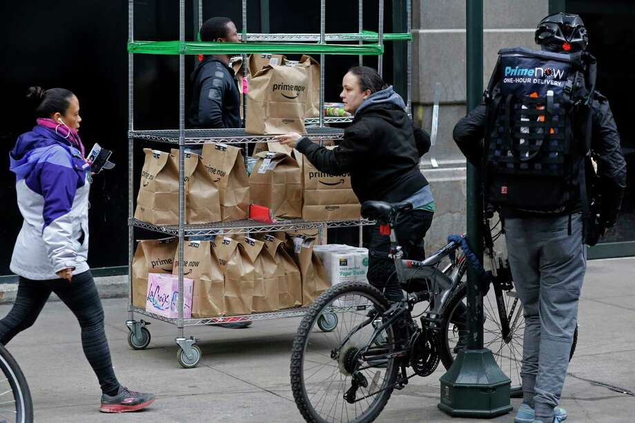 In this Wednesday, Dec. 20, 2017, photo, a clerk rolls a cart full of customer orders while a bicyclist with a backpack of orders prepares to leave the Amazon Prime warehouse, in New York. (AP Photo/Mark Lennihan) Photo: Mark Lennihan / Copyright 2017 The Associated Press. All rights reserved.