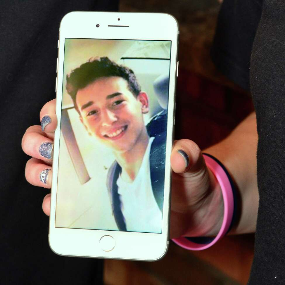 Niko DiNovo's cousin Darianna Resciniti with a photo of Niko on her phone at Niko's Pizzaria and Deli Wednesday Dec. 20, 2017 in Colonie, NY. (John Carl D'Annibale / Times Union)