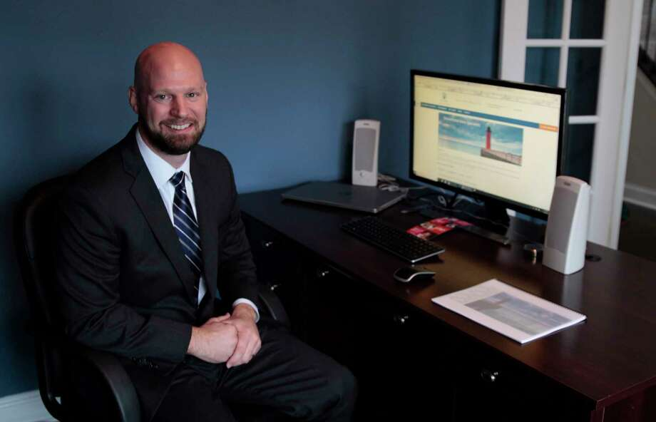 In this Dec. 20, 2017 photo, Justin Dopierala sits in his home office of DOMO Capital Management, LLC in Germantown, Wisc. Anticipating the passage of the Republican tax plan, he said he spent $20,000 on business improvements over the last couple months, including a new website and marketing pitch book for potential clients, included in this photo. Dopierala expects to have a nearly $11,000 reduction in taxes on his $150,000 income. He said he generally votes for Republicans and voted for Trump, partly expecting he would pass a new tax plan. (AP Photo/Carrie Antlfinger) Photo: Carrie Antlfinger / Copyright 2017 The Associated Press. All rights reserved.