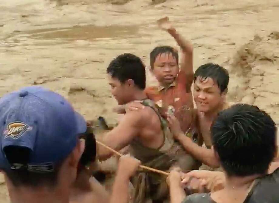 In this photo made from video by Aclimah Disumala, Friday, Dec. 22, 2017, villagers cross raging flood waters in Lanao del Norte, Zamboanga Pennisula, southern Philippines. A tropical storm has unleashed flash floods and set off landslides in the southern Philippines leaving dozens of people dead. (Aclimah Disumala via the AP) Photo: Aclimah Disumala / Aclimah Disumala