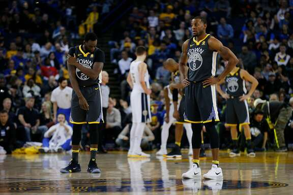 Golden State Warriors forward Draymond Green (23) and Golden State Warriors forward Andre Iguodala (9) during the first half of an NBA basketball game between the Golden State Warriors and the Denver Nuggets at Oracle Arena on Saturday, Dec. 23, 2017 in Oakland, Calif. The Nuggets lead 53-41 at half.
