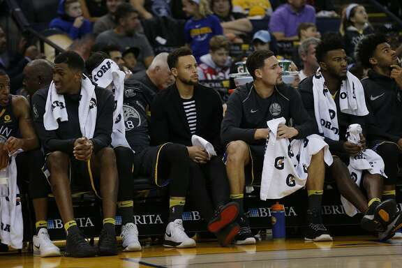 Golden State Warriors guard Stephen Curry (30) watches from the bench during the first half of an NBA basketball game between the Golden State Warriors and the Denver Nuggets at Oracle Arena on Saturday, Dec. 23, 2017 in Oakland, Calif. The Nuggets lead 53-41 at half.