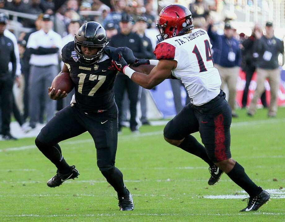 Army quarterback Ahmad Bradshaw (17) tries to break free from San Diego State safety Tariq Thompson (14) during the first half of the Armed Forces Bowl in an NCAA college football game in Fort Worth, Texas, S (Steve Nurenberg/Star-Telegram via AP) Photo: Steve Nurenberg / Star-Telegram