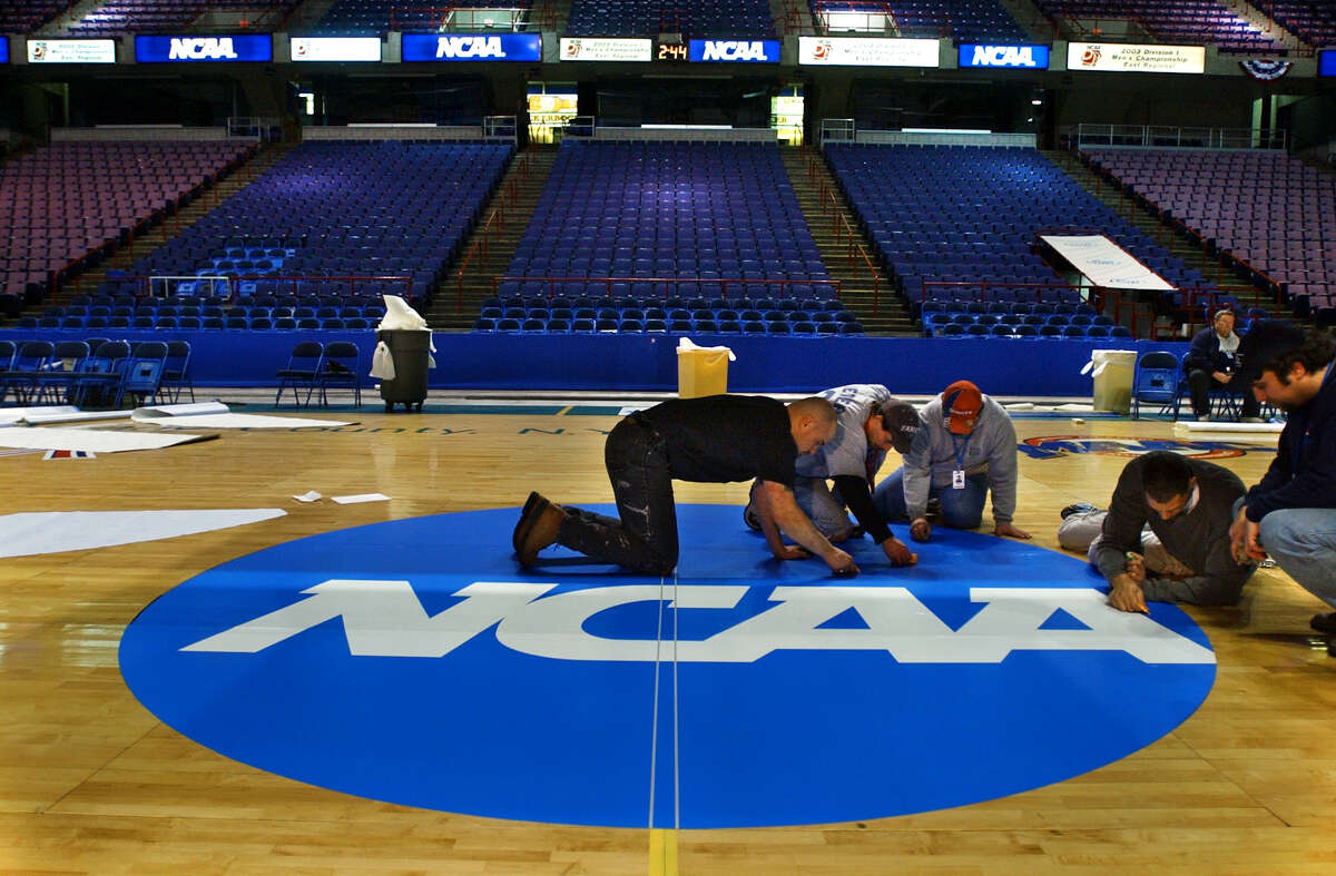 Pepsi Arena employees, from left to right; Jose Soler, Scott Wieczorkowski, Rick Lennox, and Nathan Sims (man at far right is unidentified) apply the finishing touches to a decal applied to center court at the Pepsi Arena on March 26, 2003, in Albany, N.Y., in preparation for this weekend's NCAA East Regional final in men's basketball. The decal has an adhesive, and will be removed at the tournament's end. (Philip Kamrass/Times Union)