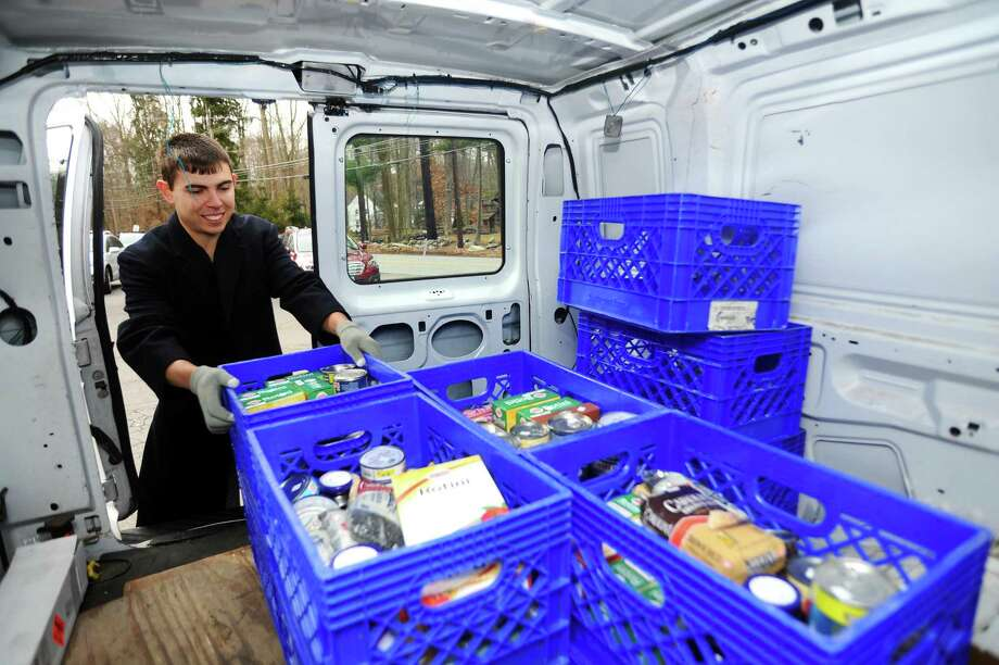 Volunteer Anthony SanFilippo,22, of Stamford, loads a New Covenant Center van at LaRocca's Country Market on Sunday. Photo: Michael Cummo / Hearst Connecticut Media / Stamford Advocate