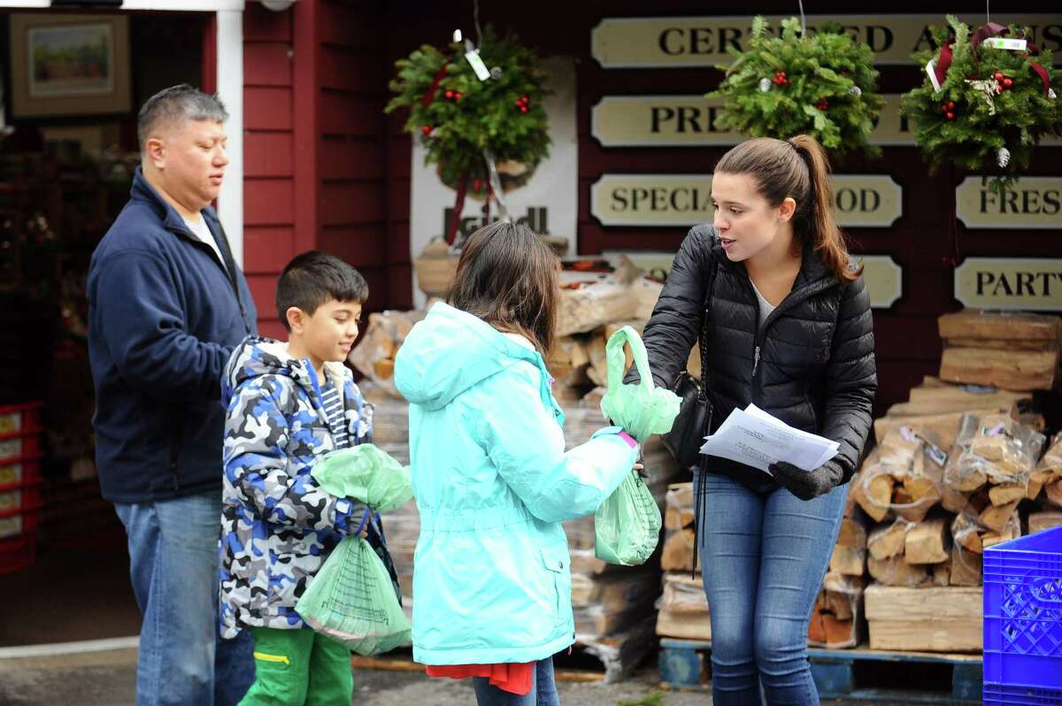 Emma Rose SanFilippo, of Stamford, takes a bag of donated food items from a shopper during the annual food drive in front of LaRocca's Country Market, hosted by the New Covenant Center, on Sunday.