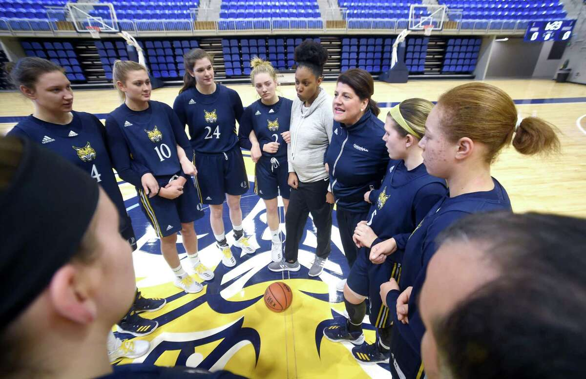 Quinnipiac women's basketball head coach Tricia Fabbri, center right, talks to her players and coaching staff at the TD Bank Sports Center in Hamden.