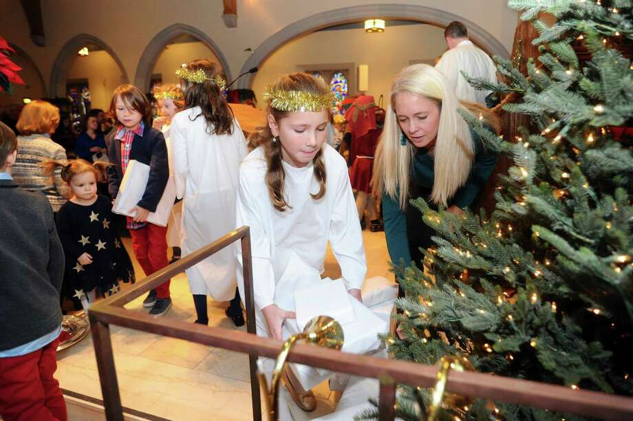 Eight-year-old Shay Sippel, center, lays a gift under the Christmas tree with Heather Sahrbeck during the Christmas Eve Children's Service inside the First Congregational Church on Sound Beach Avenue in Greenwich, Conn. on Sunday, Dec. 24, 2017. Photo: Michael Cummo / Hearst Connecticut Media / Stamford Advocate