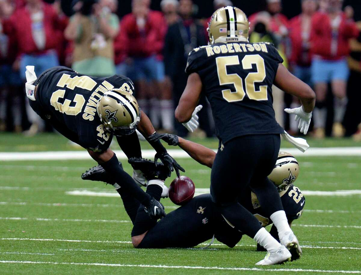 New Orleans Saints free safety Marcus Williams (43) grabs an interception s the ball lands on the back of cornerback Marshon Lattimore (23) as outside linebacker Craig Robertson (52) comes in to assist in the first half of an NFL football game against the Atlanta Falcons in New Orleans, Sunday, Dec. 24, 2017. (AP Photo/Bill Feig)