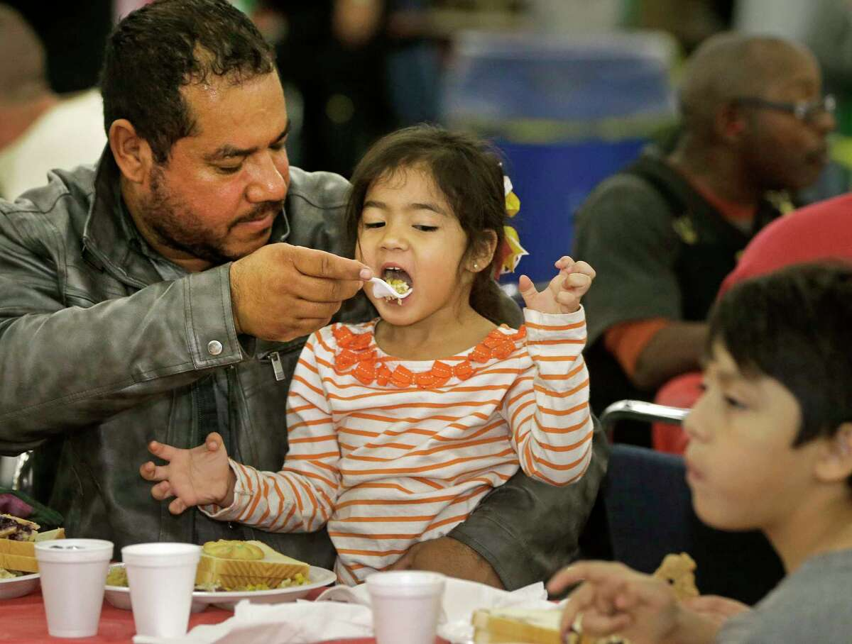 Reynaldo Mathis, feeds his daughter, Madisson Mathis, 3, during of the City Wide Club 39th Annual Christmas Eve Big Feast held at George R. Brown Convention Center, 1001 Avenida De Las Americas, Saturday, Dec. 23, 2017, in Houston.