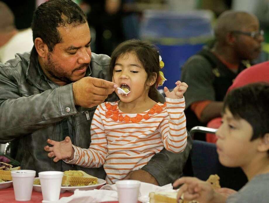 Reynaldo Mathis, feeds his daughter, Madisson Mathis, 3, during of the City Wide Club 39th Annual Christmas Eve Big Feast held at George R. Brown Convention Center, 1001 Avenida De Las Americas, Saturday, Dec. 23, 2017, in Houston. Photo: Melissa Phillip, Houston Chronicle / © 2017 Houston Chronicle