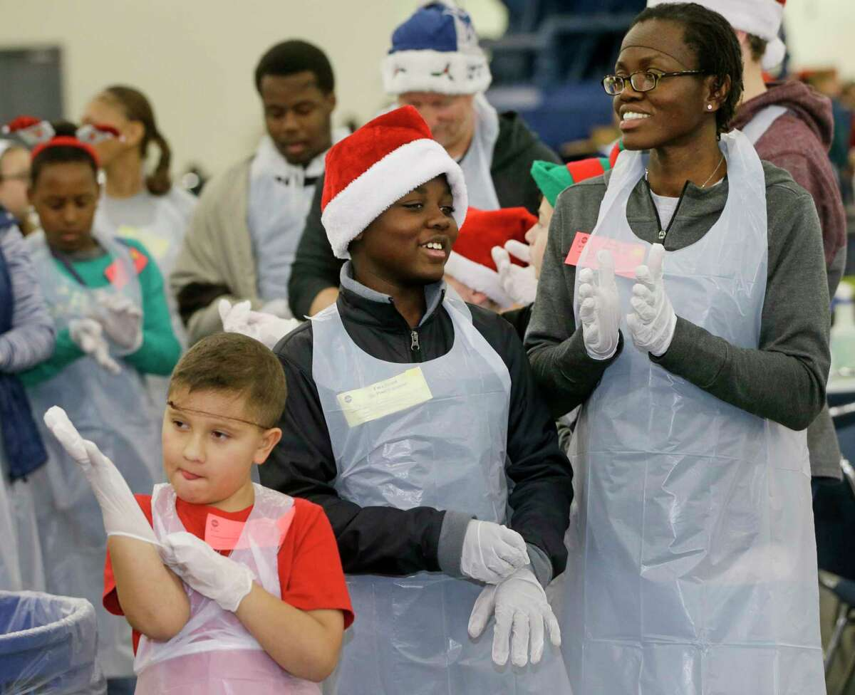 Volunteers Julian Jarve, 9, left, DeShawn Pittman, 11, and his mother, Denise Pittman, right, prepare to help serve food during the City Wide Club 39th Annual Christmas Eve Big Feast held at George R. Brown Convention Center, 1001 Avenida De Las Americas, Saturday, Dec. 23, 2017, in Houston.