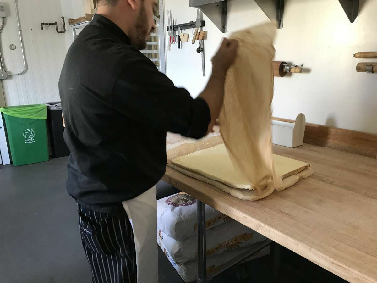 After the dough is mixed and rested, a block of butter is placed onto the dough before being pressed and folded in.