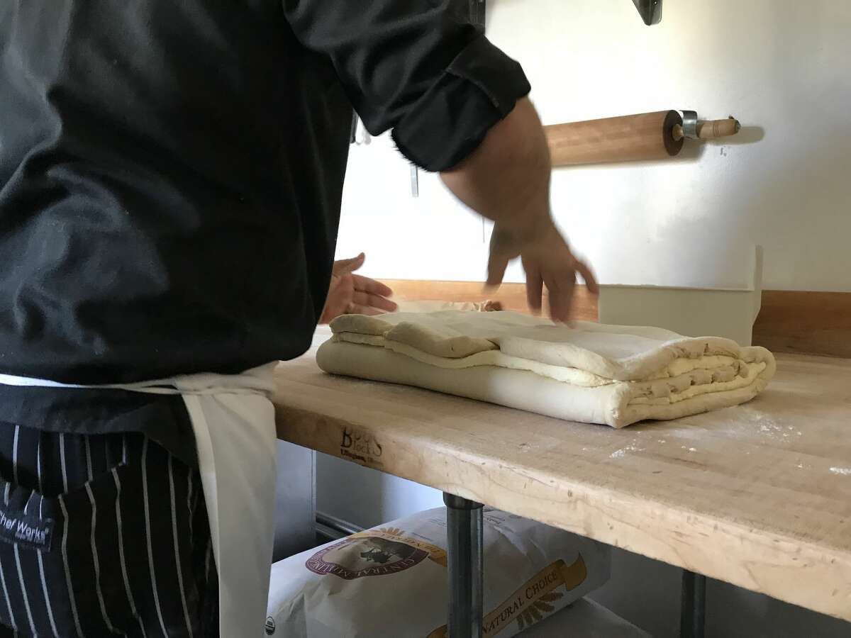 Butter can be seen amongst the layers of folded dough, as Viennoiserie Director Fausto Echeverria works it before heading back to the press machine.
