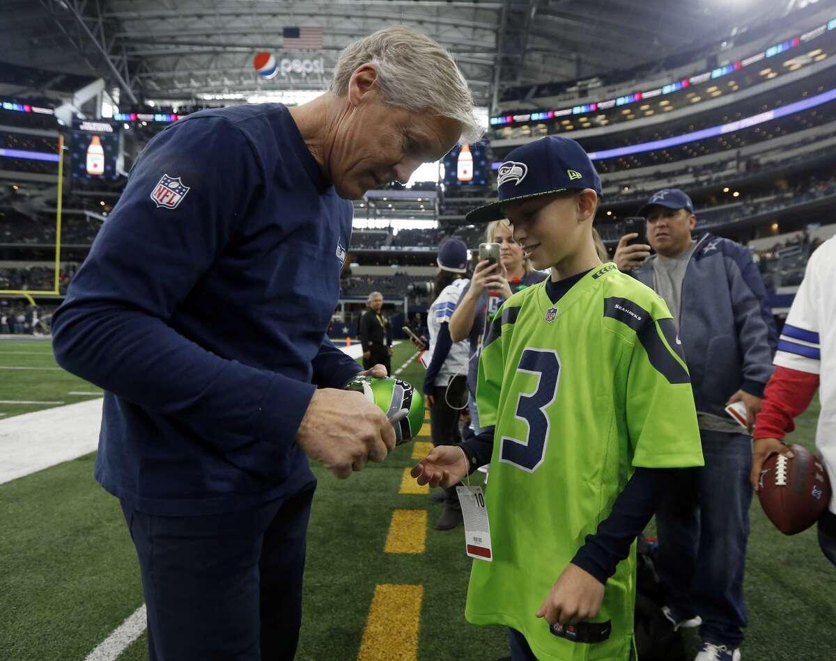 Seattle Seahawks head coach Pete Carroll, left, autographs a football for Braylon Vega, right, of Lovington, N.M., before an NFL football game agains the Dallas Cowboys, Sunday, Dec. 24, 2017, in Arlington, Texas. (AP Photo/Michael Ainsworth)