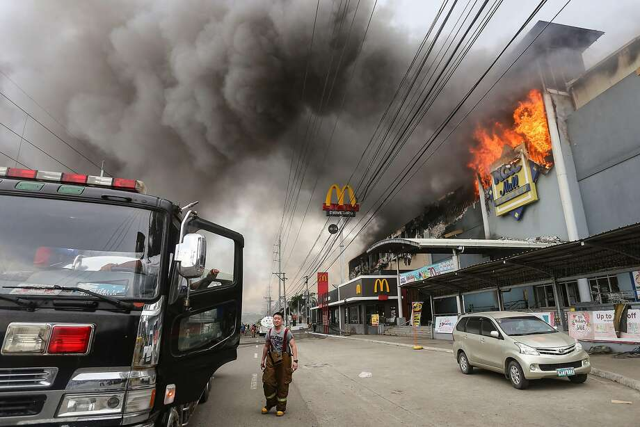 This photo taken on December 23, 2017 shows a firefighter standing in front of a burning shopping mall in Davao City on the southern Philippine island of Mindanao.  Thirty-seven people were believed killed in a fire that engulfed a shopping mall in the southern Philippine city of Davao, local authorities said on December 24. Photo: MANMAN DEJETO, AFP/Getty Images