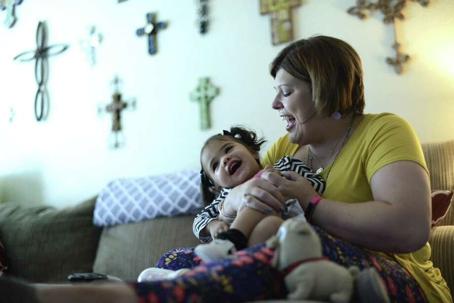 Libby Querry was foster mother to this child whom she named Mia after adopting her through The Children's Center. Libby Querry is now a single mother with a career and parents who are very supportive in caring for their new grandchild. They enjoy each other at home on Tuesday, Nov. 21, 2017. Photo: Billy Calzada / San Antonio Express-News / San Antonio Express-News