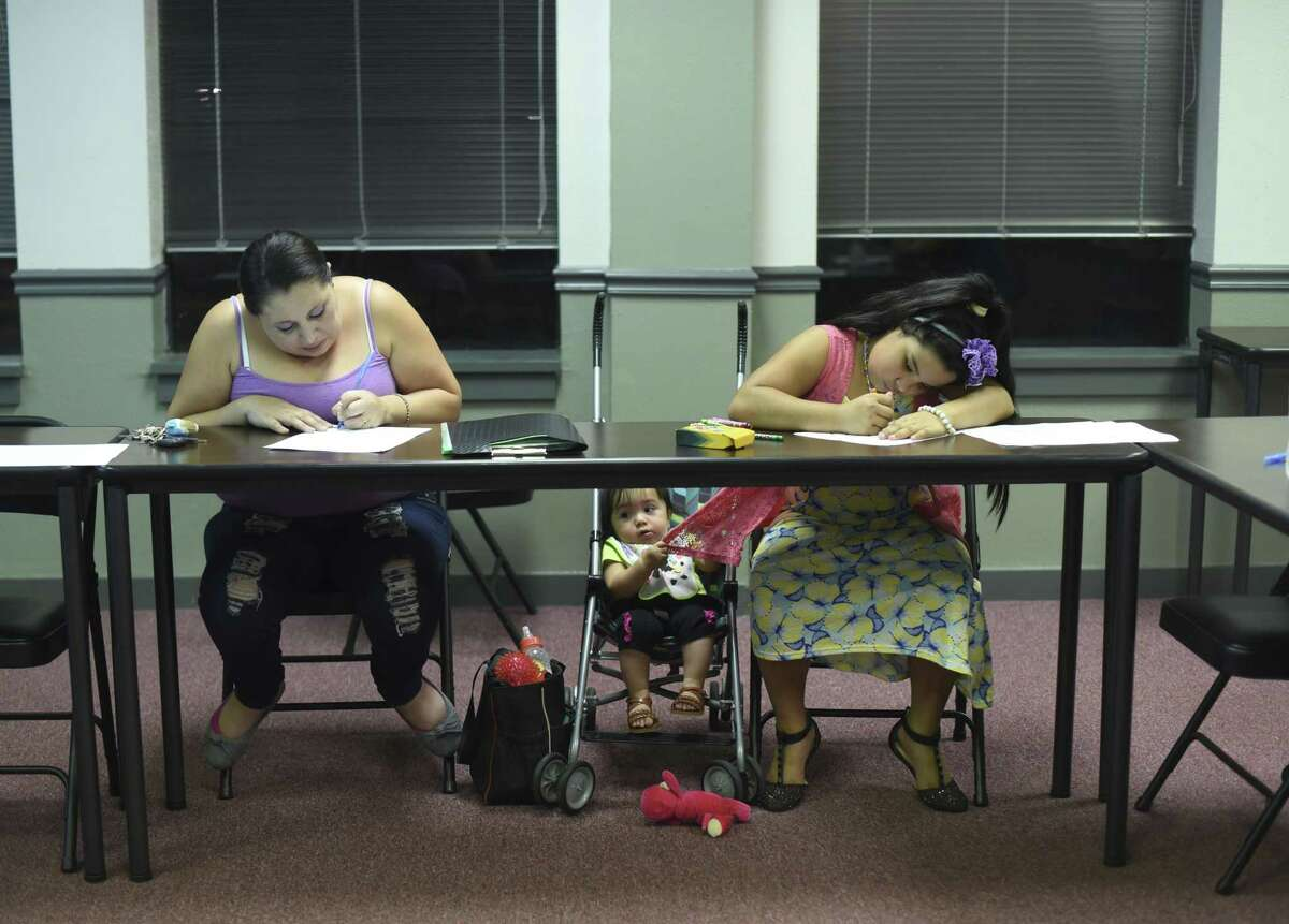 Mary Rosas attends a class with her daughters at the Mexican American Unity Council, which is creating a housing center.
