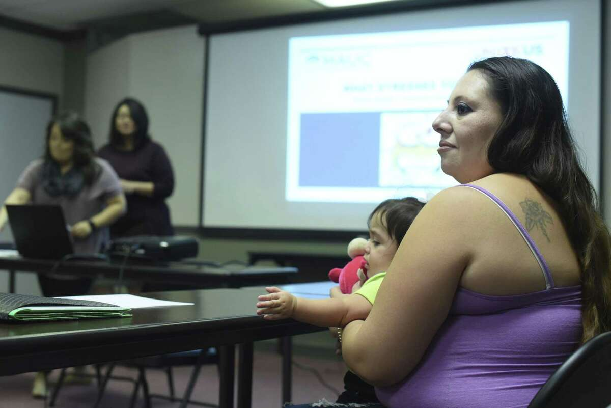 """Mary Rosas attends a class called """"What Stresses You Out?"""" as she holds her daughter, nine-month-old Neaveh, at Mexican American Unity Council on Nov. 21, 2017."""