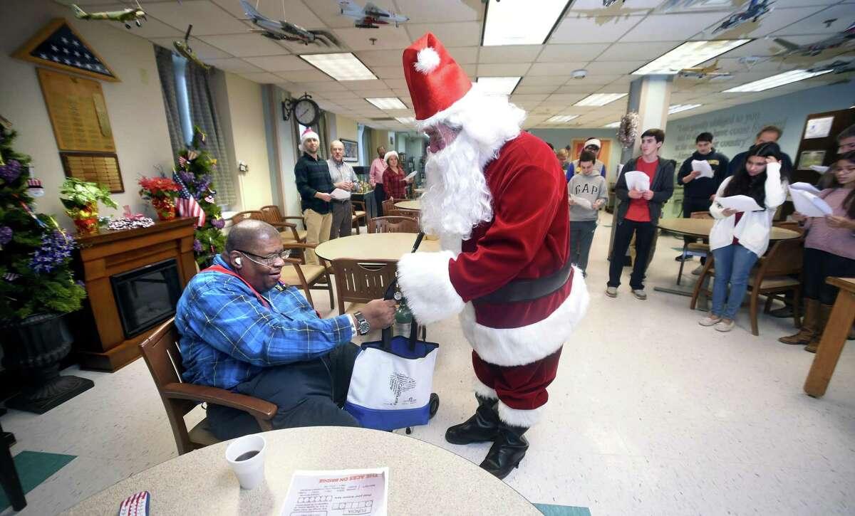 Bobby Highsmith, left, gets gifts from Mike Romeo of B'nai Brith International as Santa Claus.