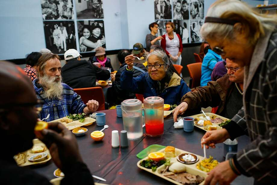 Marilyn Chan (center) raises a piece of food to cheer to a free lunch at Glide Memorial Church with meat donated by the House of Prime Rib. Photo: Gabrielle Lurie, The Chronicle