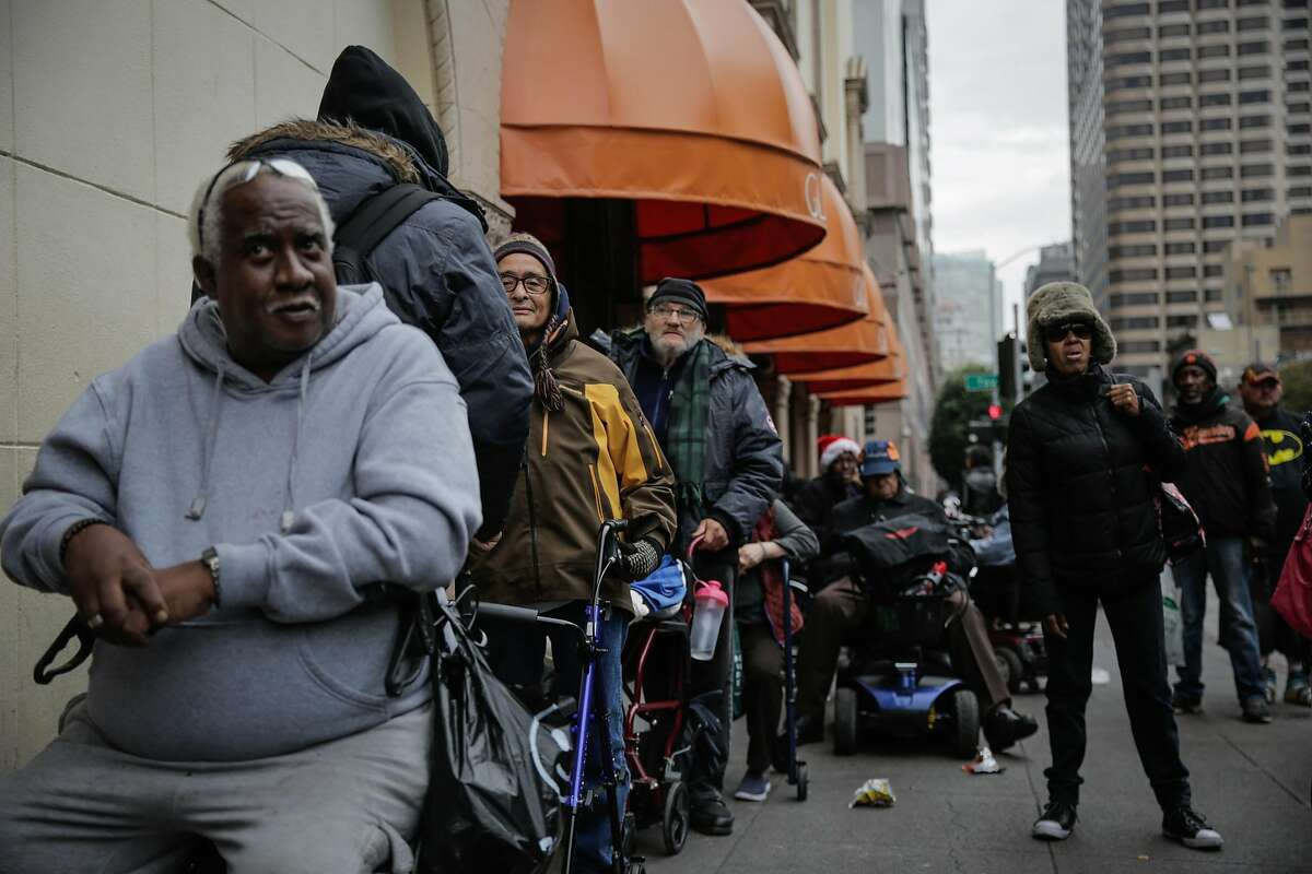 Laurence Heard (left) and other clients wait outside Glide Memorial Church ahead of a free Christmas Eve lunch hosted by House of Prime Rib in San Francisco, Calif., on Sunday, Dec. 24, 2017.