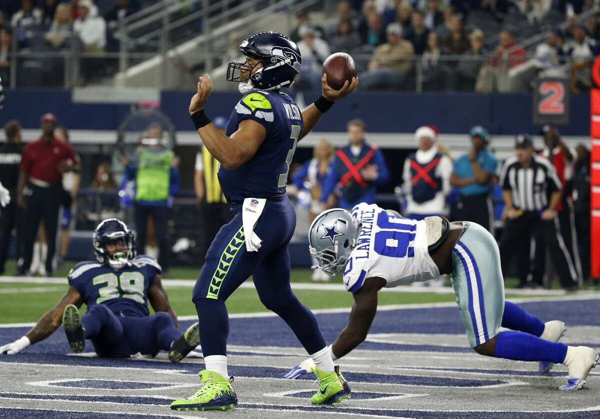 Seattle Seahawks quarterback Russell Wilson (3) throws a pass as Dallas Cowboys defensive end DeMarcus Lawrence (90) pressures in the first half of an NFL football game, Sunday, Dec. 24, 2017, in Arlington, Texas. (AP Photo/Ron Jenkins)