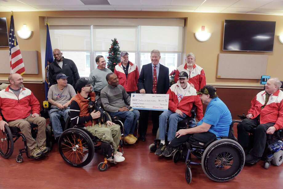 Douglas Bauer, center, CEO of All Square Wealth Management, talks with veterans during an event at the Stratton VA Medical Center on Wednesday, Dec. 13, 2017, in Albany, N.Y.  Bauer made a cash donation to the Albany Team Adaptive Sports.   (Paul Buckowski / Times Union) Photo: PAUL BUCKOWSKI / 20042226A