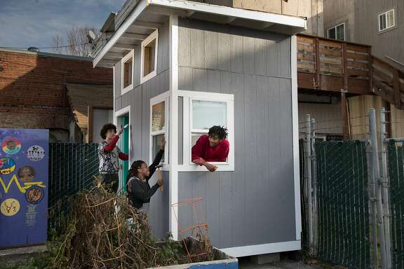 Stormy Adams, 16, Mary Stackienicz and Onynex Johnson touch up their tiny home prototype on Friday, Dec. 22, 2017 in Berkeley, CA.  They hope to build 25 total tiny homes in a village for homeless youths.