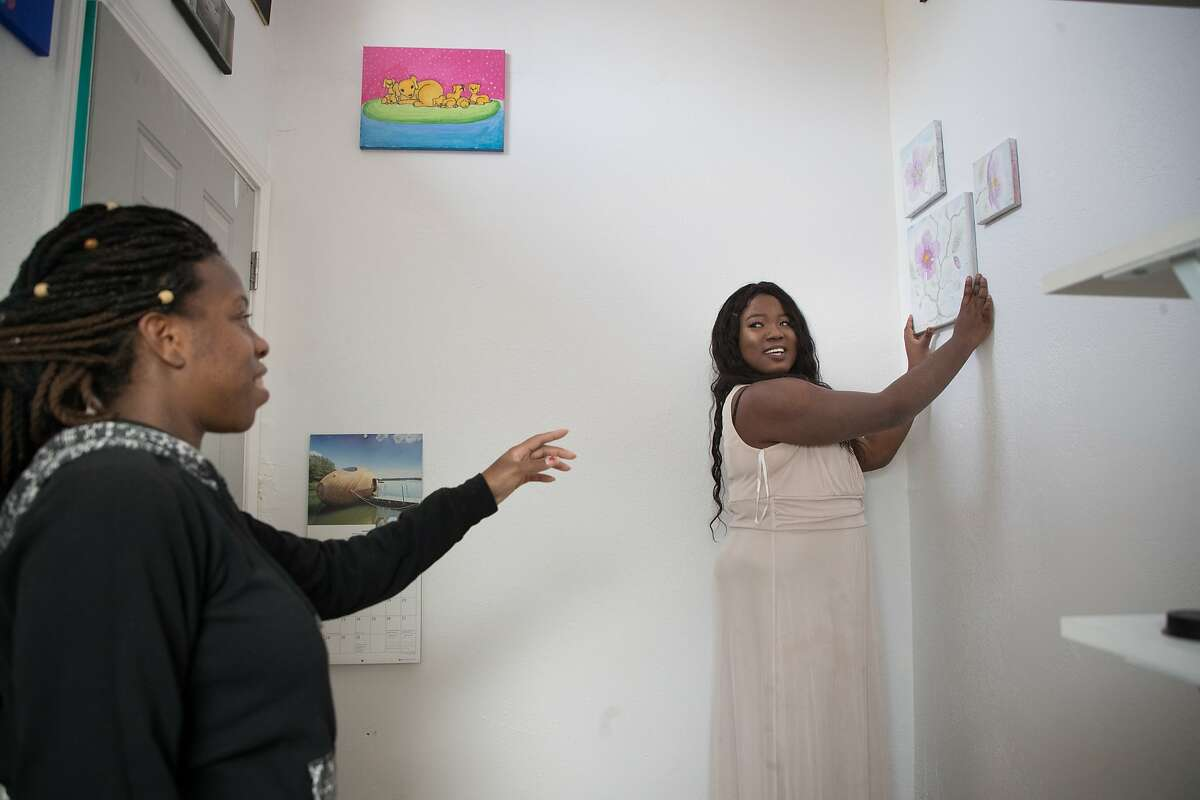 Mary Stackienicz helps Mame Diarra Abdur-Rahman adjust art in the prototype tiny home they built on Friday, Dec. 22, 2017 in Berkeley, CA. They hope to build 25 total tiny homes in a village for homeless youths.