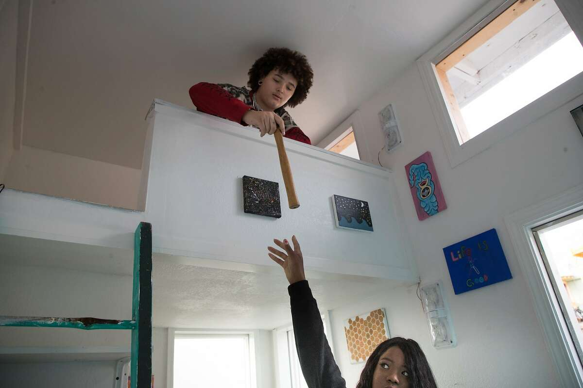 Stormy Adams, 16, in the bedroom loft, hands a hammer to Mame Diarra Abdur-Rahmanwork on Friday, Dec. 22, 2017 in Berkeley, CA. They hope to build 25 total tiny homes in a village for homeless youths.