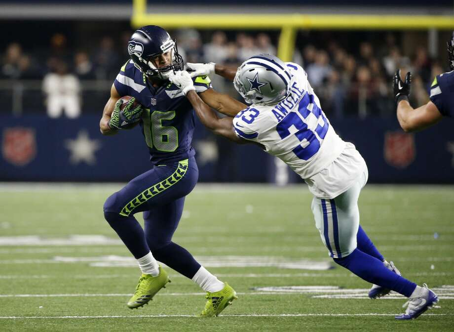 Seattle Seahawks wide receiver Tyler Lockett (16) carries the ball as his face masked is grabbed by Dallas Cowboys cornerback Chidobe Awuzie (33) in the second half of an NFL football game, Sunday, Dec. 24, 2017, in Arlington, Texas. (AP Photo/Michael Ainsworth) Photo: Michael Ainsworth/AP