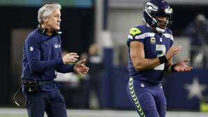 Seattle Seahawks head coach Pete Carroll and quarterback Russell Wilson walk onto the field in the second half of an NFL football game against the Dallas Cowboys on Sunday, Dec. 24, 2017, in Arlington, Texas. (AP Photo/Michael Ainsworth)
