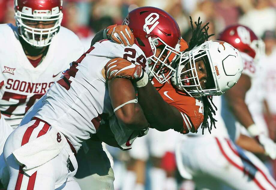 Longhorns linebacker Malik Jefferson brings down Rodney Anderson as Texas plays Oklahoma in the Red River Showdown at the Cotton Bowl on Oct. 14. Photo: Tom Reel, Staff / 2017 SAN ANTONIO EXPRESS-NEWS