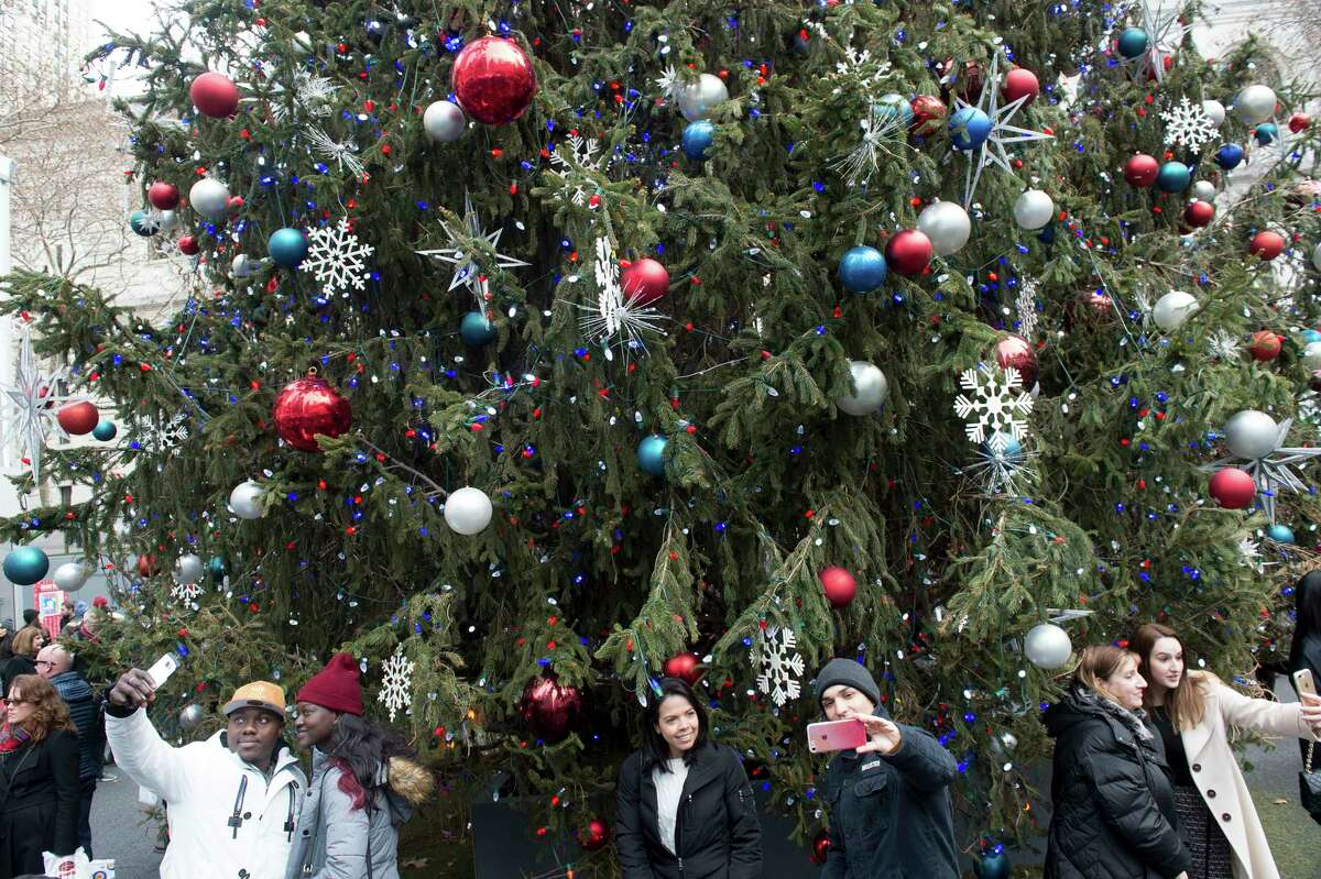 People take photos at the Christmas tree at Bryant Park in New York, Dec. 24, 2017. (Bryan R. Smith/The New York Times)