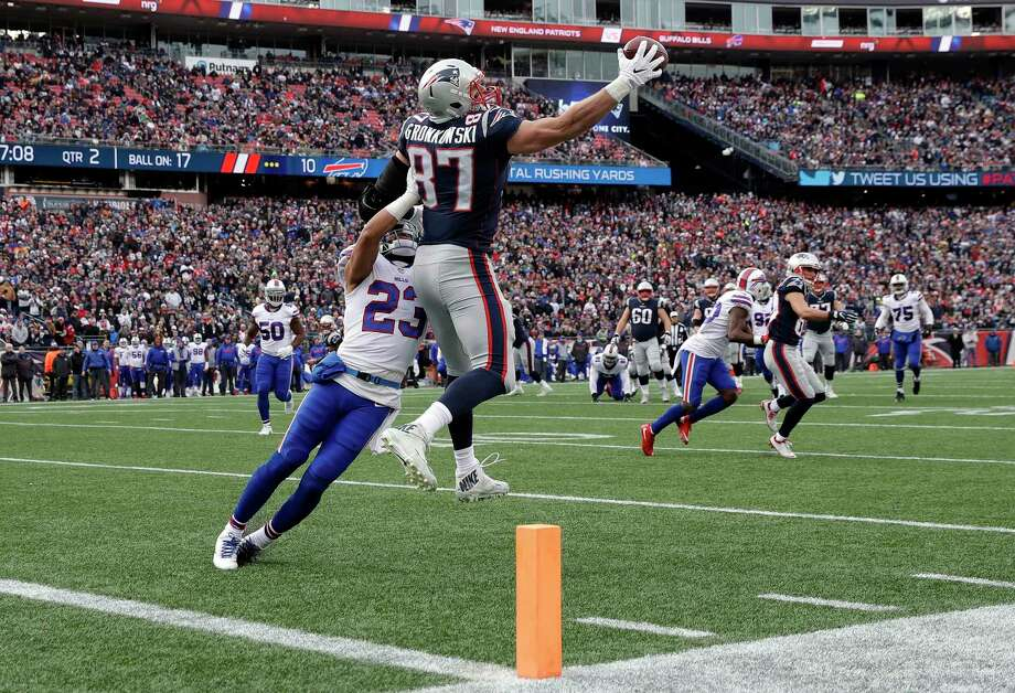 New England Patriots tight end Rob Gronkowski (87) makes a one-handed catch of a Tom Brady pass, as Buffalo Bills safety Micah Hyde (23) defends, before running for a touchdown during the first half of an NFL football game, Sunday, Dec. 24, 2017, in Foxborough, Mass. (AP Photo/Charles Krupa) Photo: Charles Krupa / Copyright 2017 The Associated Press. All rights reserved.