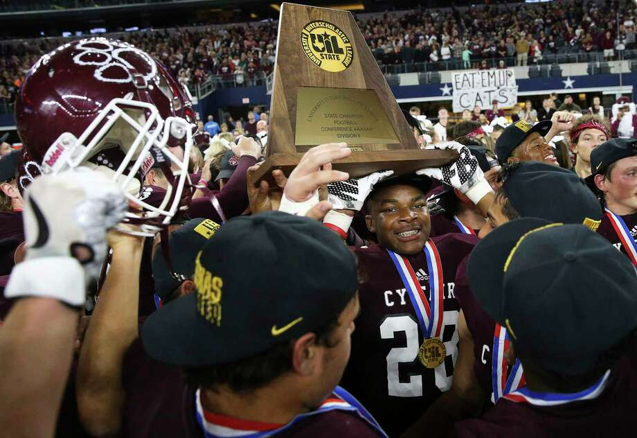 Cy-Fair Marcus McKinley (28) helps holding the state title plaque during celebrationg after winning the Class 6A Division II State Championship Game at AT&T Stadium on Saturday, Dec. 23, 2017, in Arlington. The Cy-Fair Bobcats defeated the Waco Midway Panthers 51-35 and won the state championship title. The Bobcats are rebuilding after graduating a massive class – they lost 41 seniors, the most in the district – but their identity is well-established. ( Yi-Chin Lee / Houston Chronicle ) Photo: Yi-Chin Lee, Houston Chronicle / © 2017  Houston Chronicle