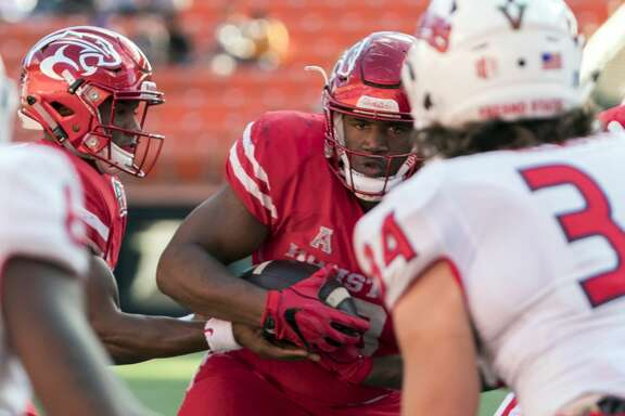 Houston defensive tackle Ed Oliver, center, manages to find an opening in the Fresno State defense to score a touchdown in the first half of the Hawaii Bowl NCAA college football game Sunday, Dec. 24, 2017, in Honolulu. (AP Photo/Eugene Tanner)