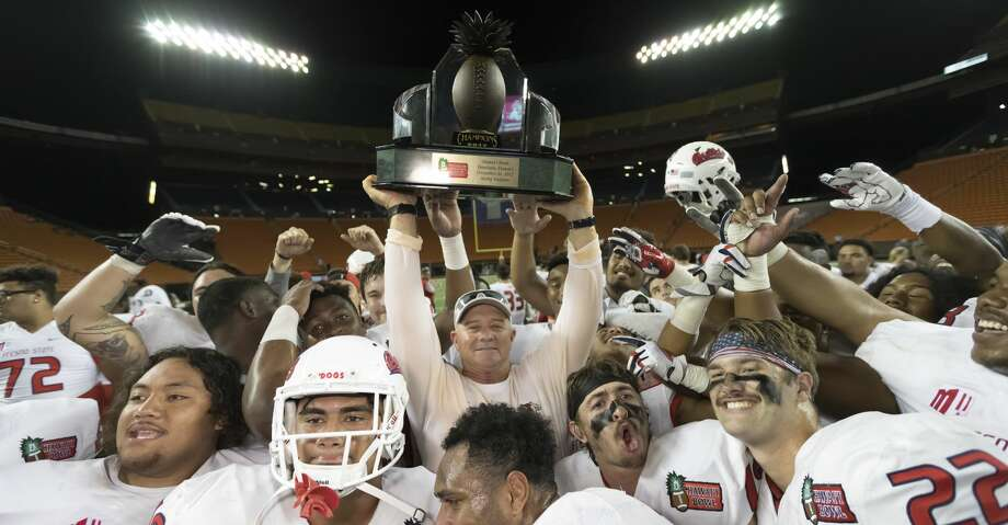 Fresno State head coach Jeff Tedford, center, holds up the Hawaii Bowl championship trophy after defeating Houston in the Hawaii Bowl NCAA college football game, Sunday, Dec. 24, 2017, in Honolulu. Fresno State won, 33-27. (AP Photo/Eugene Tanner) Photo: Eugene Tanner/Associated Press