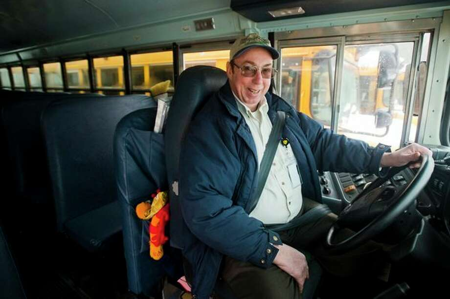 Steve Jenkins, a bus driver for the Bullock Creek Schools, poses for a portrait inside his bus last week. For the last two years, Jenkins has brought smiles and joy to each student that rides his bus by passing out Christmas gift bags that include gift cards and cash. (Katy Kildee/kkildee@mdn.net)