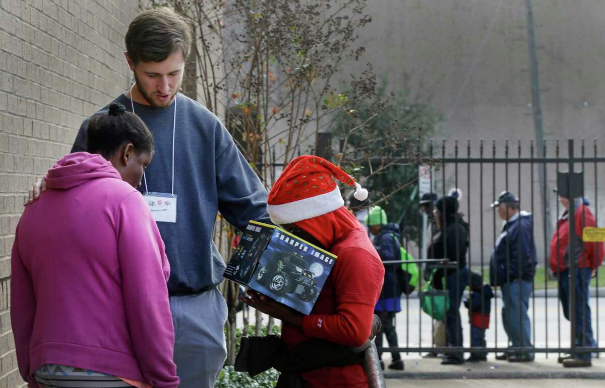 Volunteer Harrison Alff, center, prays with Bunnie Adair, left, and her godson, Cristian Williams, 11, as they leave after having their Christmas meal at The Salvation Army Family Residence, 1603 McGowen, Monday, Dec. 25, 2017, in Houston. Cristian is holding a remote control car he was given during the event. In the background, a line of people waiting outside to be let inside to eat is shown.