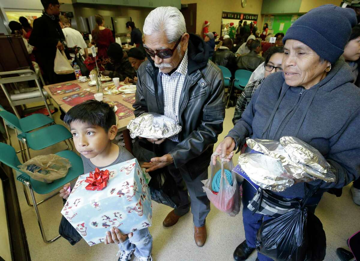 Angel Acevedo, 7, carries a Christmas present as he leaves with his grandparents, Rodolfo Lagunas and Domidela Lagunas after having a Christmas meal at The Salvation Army Family Residence, 1603 McGowen, Monday, Dec. 25, 2017, in Houston.