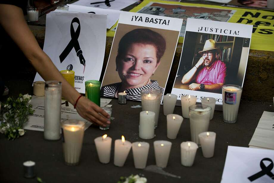 A woman places a candle in front of pictures of murdered journalists Miroslava Breach, left, and Javier Valdez during a demonstration against the killing of journalists, outside the Interior Ministry in Mexico City. Photo: Rebecca Blackwell, Associated Press