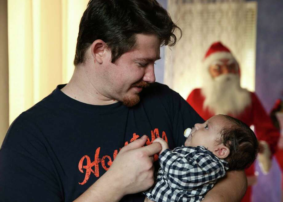 Michael Cassidy, 26, tends his sleepy two-month-old son, Azrael Cassidy, after posing for a portrait on Sunday, Dec. 10, 2017, in Houston. A special medical tourniquet device saved Cassidy when he was involved in a bad motorcycle accident back in March, and now he would be celebrating Christmas with his fiance, Alexis Garcia, 22, and their new family. Photo: Yi-Chin Lee, Houston Chronicle / © 2017  Houston Chronicle