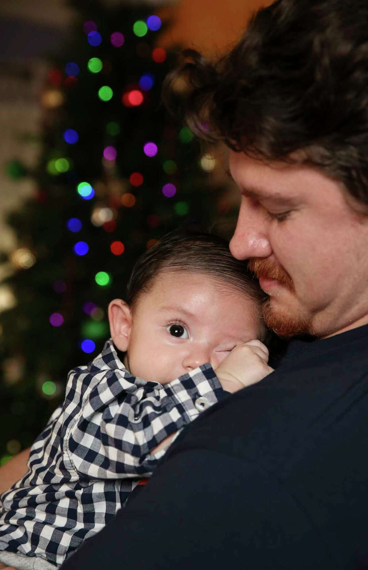 Michael Cassidy, 26, tends his sleepy two-month-old son, Azrael Cassidy, while posing for a portrait on Sunday, Dec. 10, 2017, in Houston. A special medical tourniquet device saved Cassidy when he was involved in a bad motorcycle accident back in March, and now he would be celebrating Christmas with his fiance, Alexis Garcia, 22, and their new family.