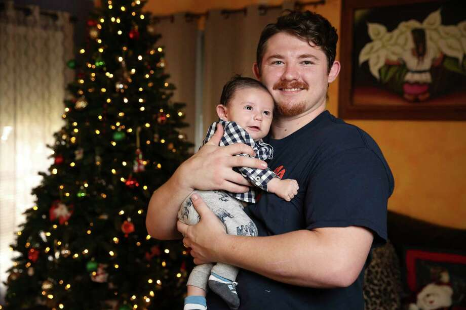 Michael Cassidy, 26, holds his two-month-old son, Azrael Cassidy, for a portrait on Sunday, Dec. 10, 2017, in Houston. A special medical tourniquet device saved Cassidy when he was involved in a bad motorcycle accident back in March, and now he would be celebrating Christmas with his fiance, Alexis Garcia, 22, and their new family. Photo: Yi-Chin Lee, Houston Chronicle / © 2017  Houston Chronicle